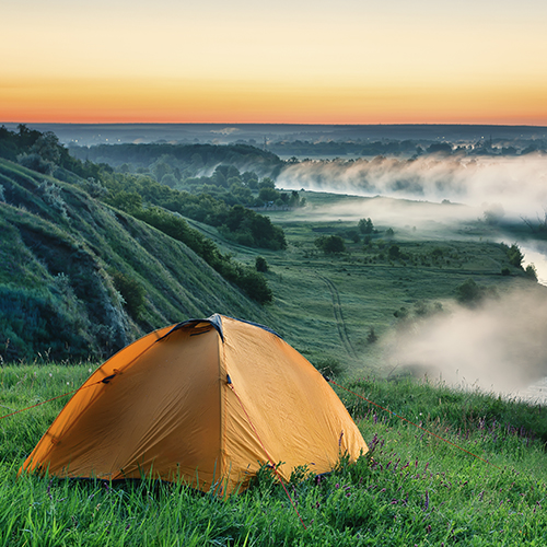 Orange tourist tent on hillside above misty river